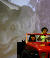 Kids enjoying T-Rex chase on a live backdrop