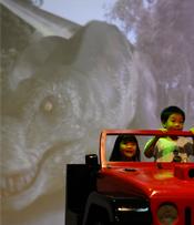 Kids enjoying T-Rex chase on a live backdrop